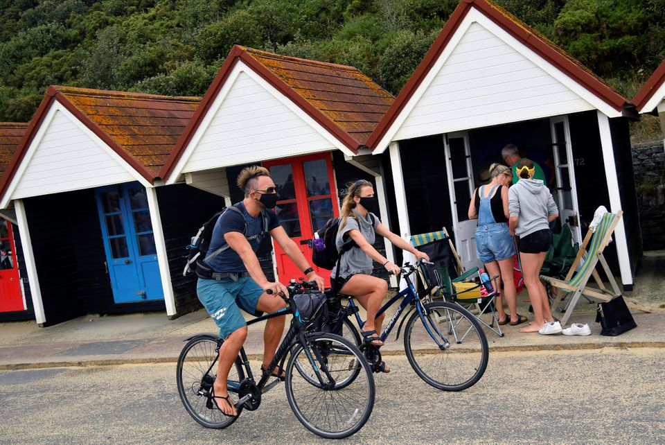People wear protective face masks as they cycle along the seafront past the beach huts in