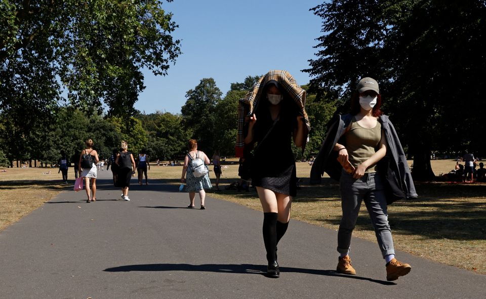 People shield themselves from the sun as they walk through Greenwich