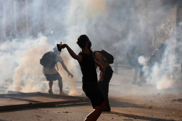 Anti-government protesters are covered by the smoke of tear gas, as they clash with riot police, during...