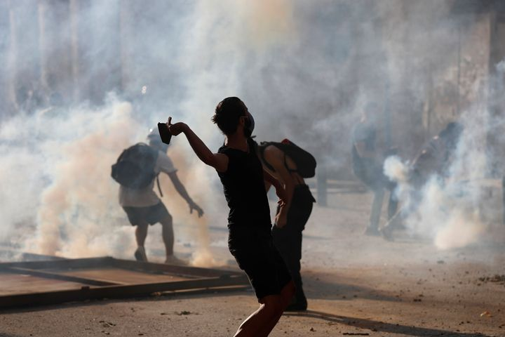 Anti-government protesters are covered by the smoke of tear gas, as they clash with riot police, during a protest against the