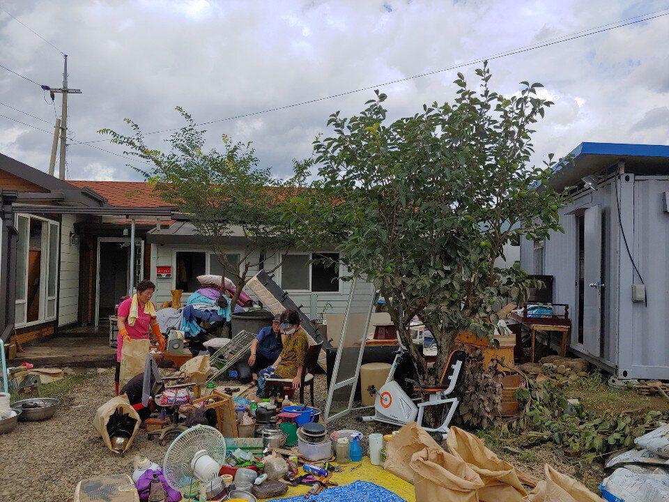 9일 오후 전남 구례군 한 마을에서 마을 주민들이 침수 피해를 입은 집을 복구하다 지쳐