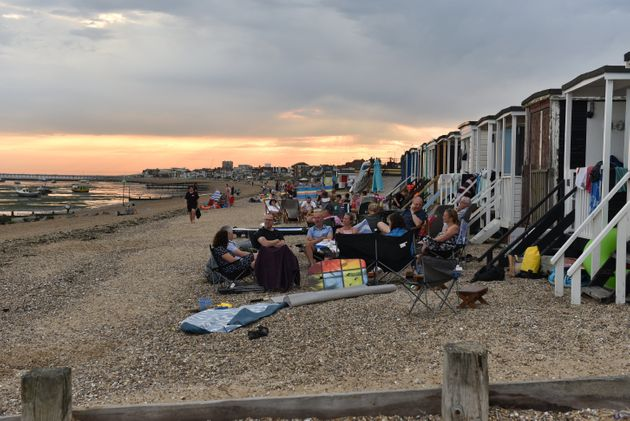 People sit on the beach into the evening as the sun set on Saturday in