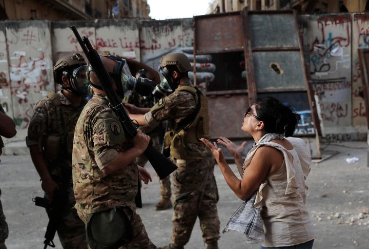 An anti-government protester, reacts in front of Lebanese soldiers during a protest against the political elites and the gove