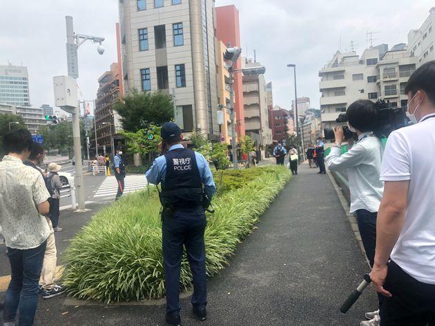 カルガモの親子を見守る警察官やメディア。カルガモの一行は、中央の茂みで一休み=東京都港区、2020年7月25日