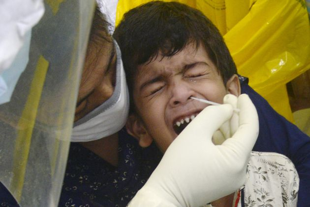 A health worker collects a swab sample from a child for antigen rapid test for Covid-19 in Kolkata on...