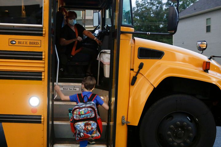 Paul Adamus, 7, climbs the stairs of a bus before the fist day of school on Monday, Aug. 3, 2020, in Dallas, Ga.  (AP Ph