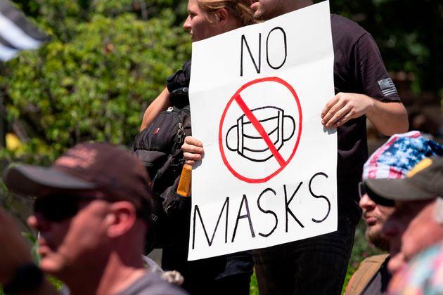 Un manifestant anti-masques brandit une pancarte en réponse aux lois locales exigeant que les...