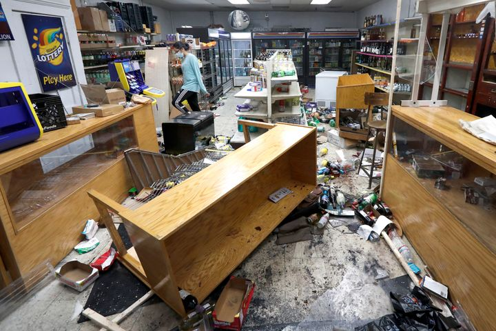 Kajal Dalal walks through her family's food and liquor store in downtown Chicago on Monday after it was vandalized.