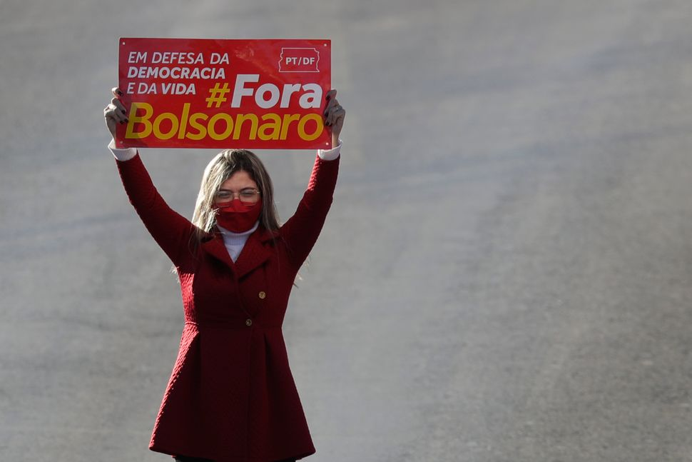 """A demonstrator holds a sign that reads """"In defense of life and democracy. Get out Bolsonaro"""" during a protest last week, as B"""