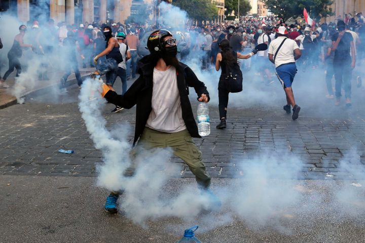 <strong>Protesters throw back tear gas canisters towards riot policemen during an anti-government protest.</strong>