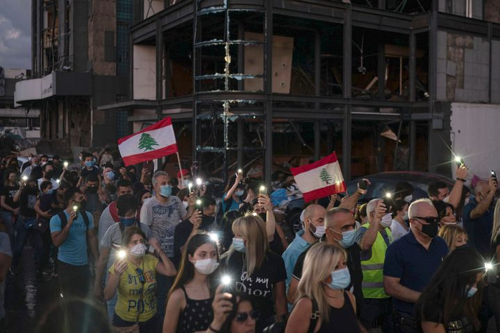 Demonstrators march past a damaged building holding candles and flashlights honoring the victims of the deadly explosion at B