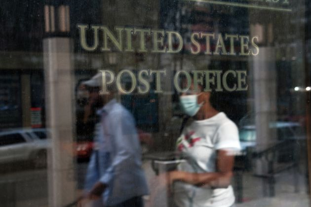 Customers walk into a Brooklyn post office last week in New York City. The U.S. Postal Service is under...