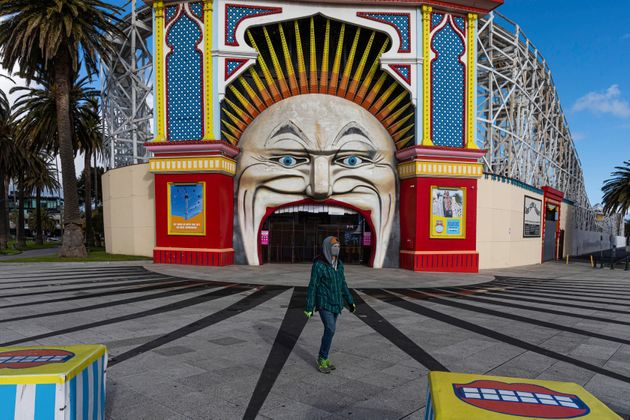 A man wearing a mask walks past Luna Park in the suburb of St Kilda during lockdown in Melbourne, Australia,...