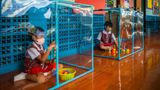 BANGKOK, THAILAND - AUGUST 10:  Thai kindergarteners wear face masks as they play in screened in play areas used for social distancing at the Wat Khlong Toey School on August 10, 2020 in Bangkok, Thailand. In the beginning of July The Wat Khlong Toey School reopened its doors to its approximately 250 students following the relaxation of lockdown measures during the COVID-19 pandemic. When the school was forced to shutter its doors in mid March due to Thailand's emergency decree and lockdown, the administration and teachers prepared measures to ensure a safe reopening. By installing sinks and soap dispensers outside of each classroom, creating social distancing screens in classrooms and lunch areas and installing hand sanitizer and temperature scanners at the entry the Wat Khlong Toey school has been open for a month and has had zero cases of COVID-19. Although Thailand is now allowing schools throughout the country to further relax safety measures, the Wat Khlong Toey school has chosen to continue strict social distancing to ensure the safety of their students and teachers. (Photo by Lauren DeCicca/Getty Images)