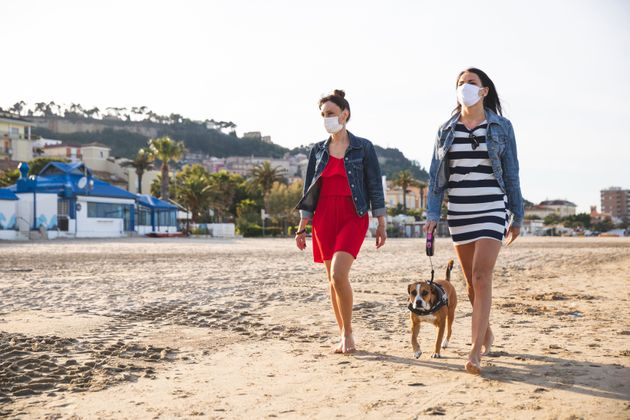 Two friends walking on the beach with dog during covid