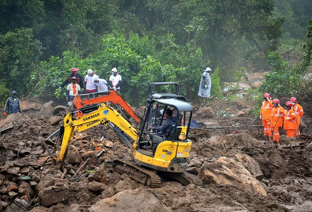 Rescue workers search for missing people at a landslide site caused by heavy rains in Pettimudy, in Kerala...