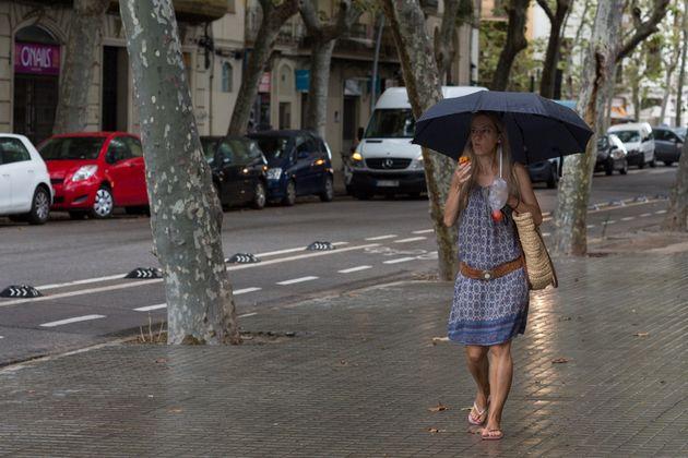 Una mujer camina por las calles lluviosas de Barcelona, en una imagen de