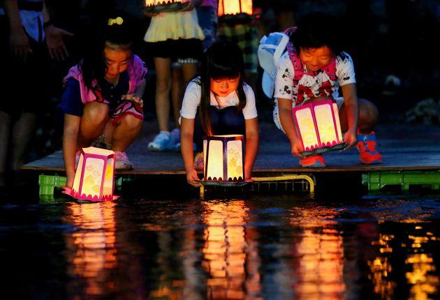 日航機墜落事故から30年となるのを前に、犠牲者の冥福を祈り、墜落現場近くの川に灯籠を流す子どもたち(2015年8月11日夜、群馬県上野村)