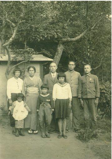 萬井家の家族写真。真ん中の白いセーラー服を着ているのが頌子さん。