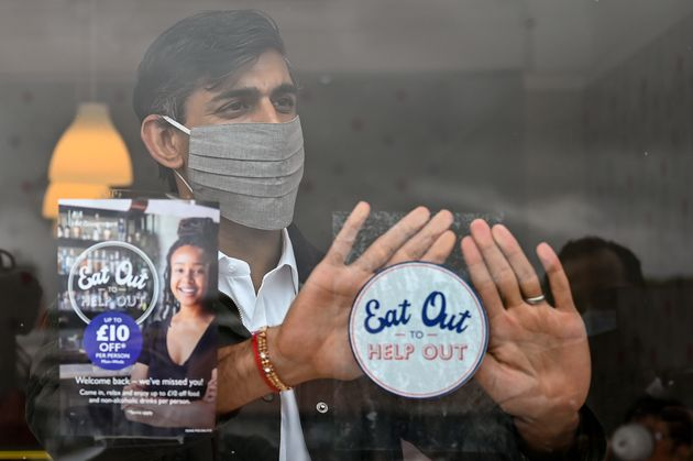Chancellor of the Exchequer Rishi Sunak places an Eat Out to Help Out sticker in the window of a business...