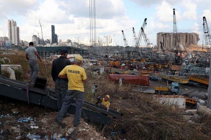 Workers remove debris from the site of last week's explosion that hit the seaport of Beirut, Lebanon, Monday, Aug. 10, 2020. (AP Photo/Bilal Hussein)
