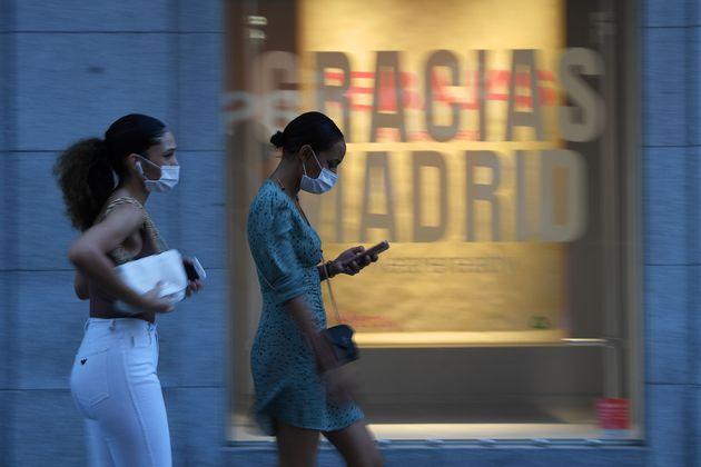 Dos mujeres con mascarilla pasan por delante de una tienda en el centro de