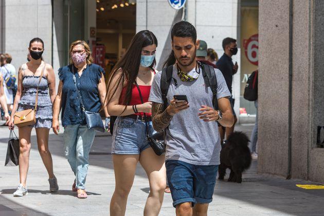Un joven camina por la calle Preciados de