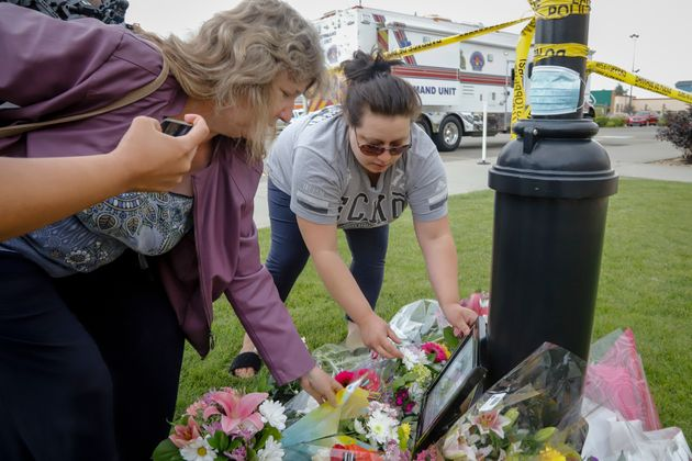 Former clinic employees Theresa Baldwin, left, and Kristen York, lay flowers at an impromptu memorial,...