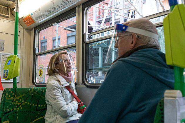 Two commuters wearing face shields are seen as they travel by tram during lockdown in Melbourne, Australia,...