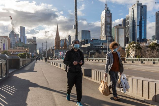 Pedestrians walk away from the central business district as lockdown due to the continuing spread of...