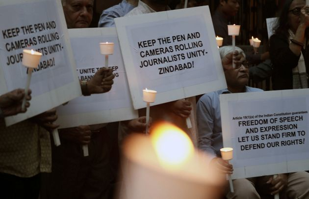 Journalists hold candles and placards during a candlelight vigil against police brutalities and attacks...