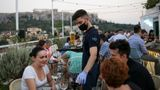 A waiter wears a protective face mask as he works in a bar, amid the spread of the coronavirus disease (COVID-19), in Athens, Greece, August 1, 2020. Picture taken August 1, 2020. REUTERS/Costas Baltas