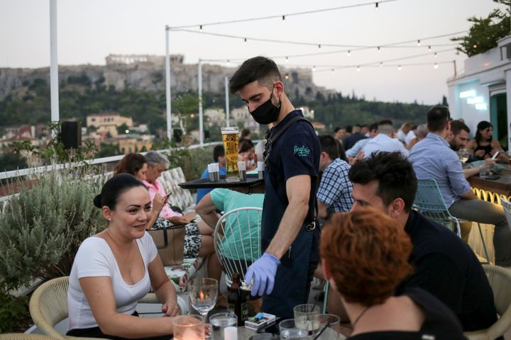 A waiter serves patrons at a bar in Athens, Greece, Aug. 1. Since the country began lifting lockdown restrictions, the number