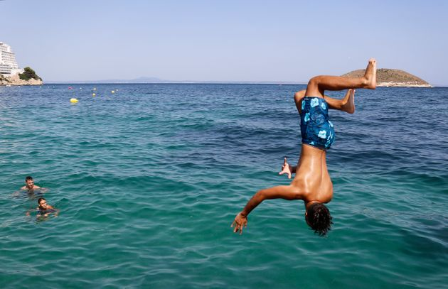 A boy jumps into the sea from the rocks of Magaluf beach on July 30 in Mallorca, Spain. The area is a...