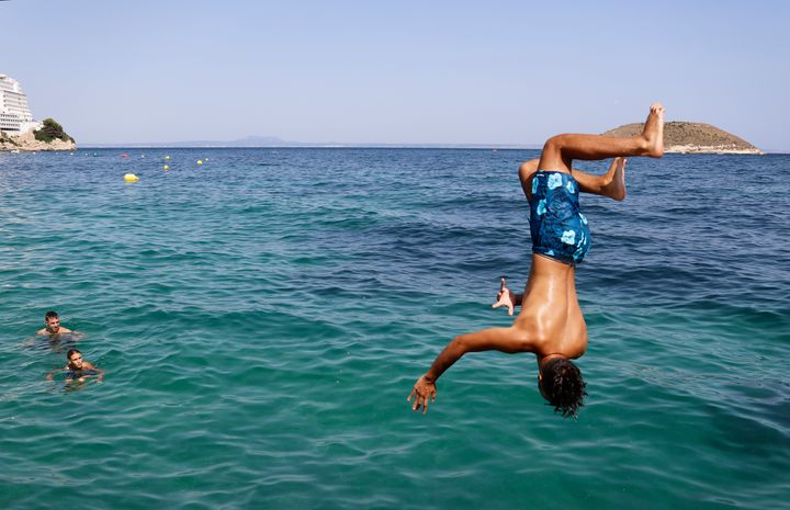 A boy jumps into the sea from the rocks of Magaluf beach on July 30 in Mallorca, Spain. The area is a popular tourist destina