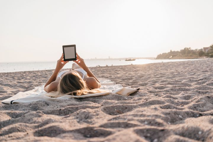 Una mujer lee en su Kindle en la playa.