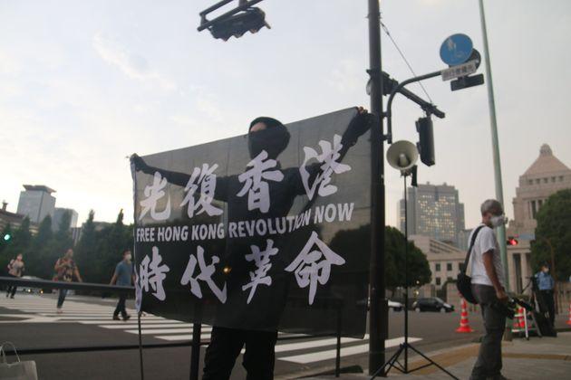国会を背に旗を掲げる参加者の男性