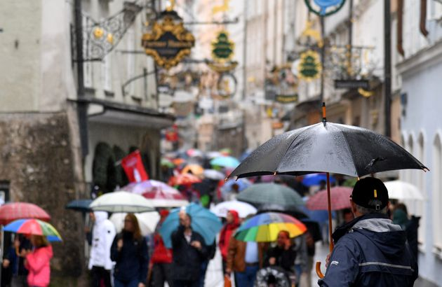 Varias personas se refugian de la lluvia bajo sus