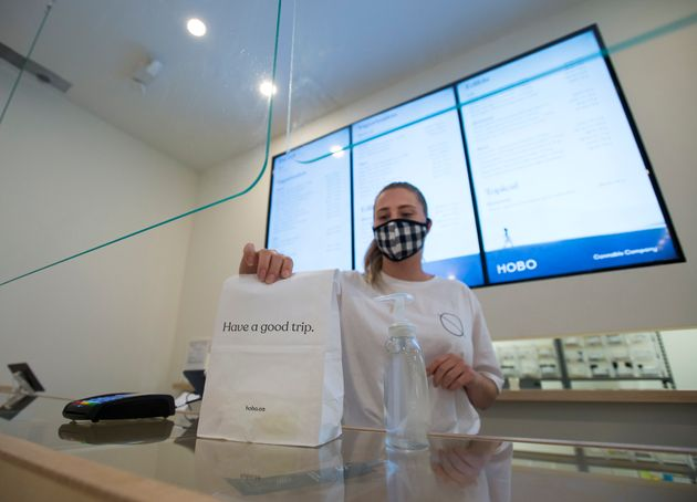 A Hobo Cannabis Company employee shows off a bag of merchandise during the COVID-19 pandemic in Toronto...