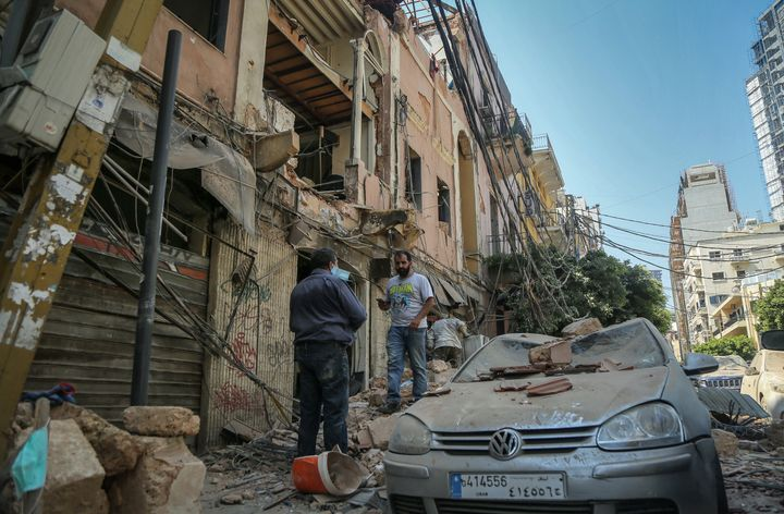 People inspect destruction outside a damaged building the day after the massive explosion.