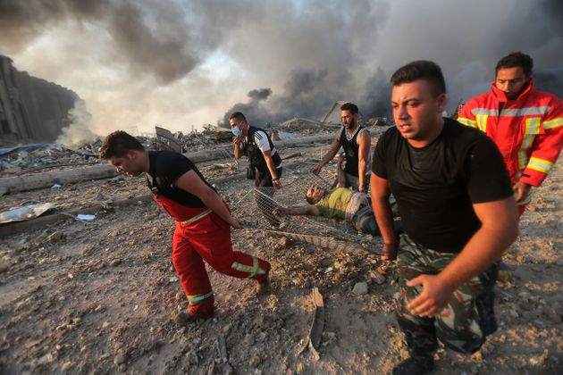 Firefighters evacuate a wounded man from the scene of an explosion at the Port of Beirut on Aug. 4,