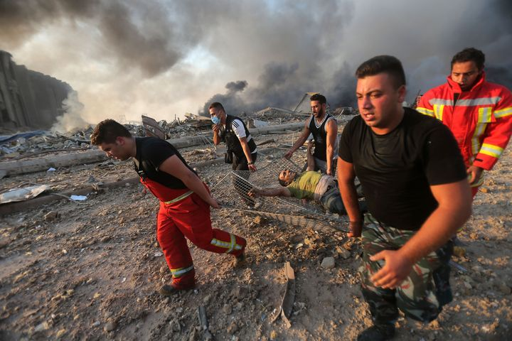 Firefighters evacuate a wounded man from the scene of an explosion at the Port of Beirut on Aug. 4, 2020.
