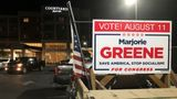 A sign showing support for construction executive Marjorie Taylor Greene, is seen on a vehicle outside an election watch event, late Tuesday, Aug. 11, 2020, in Rome, Ga. Greene, criticized for promoting racist videos and adamantly supporting the far-right QAnon conspiracy theory, won the GOP nomination for northwest Georgia's 14th Congressional District. (AP Photo/Mike Stewart)