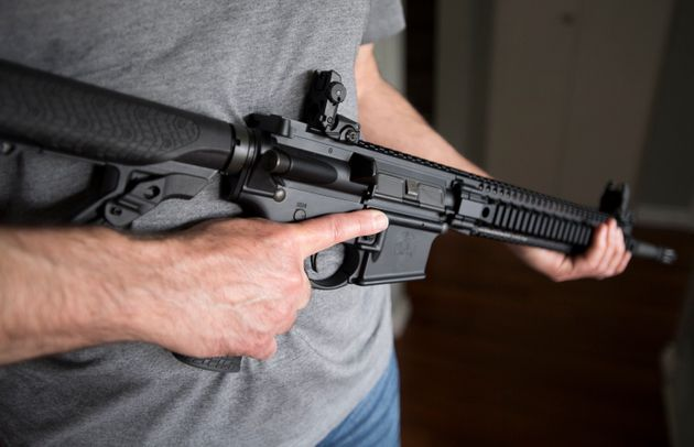 A restricted gun licence holder holds a AR-15 at his home in Langley, B.C., on May 1,