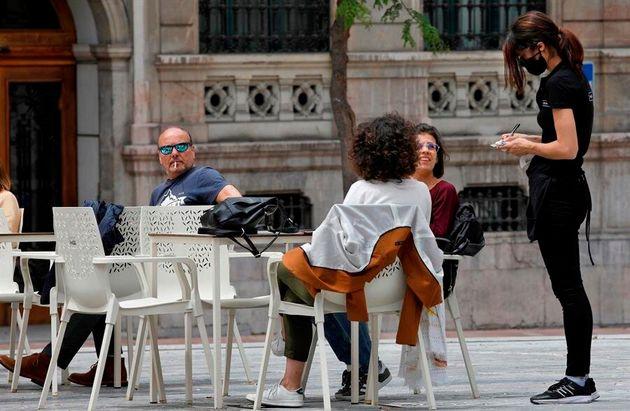 Un hombre fuma en una terraza de un bar de