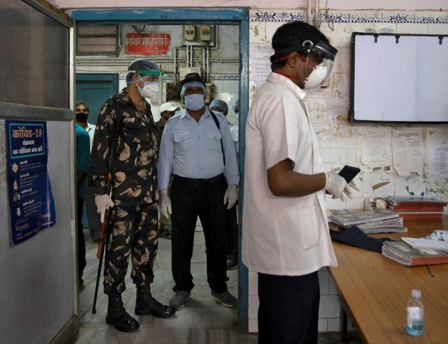 Armed security personnel stand guard as Dr. Kumar Gaurav speaks to his colleagues on the emergency ward...