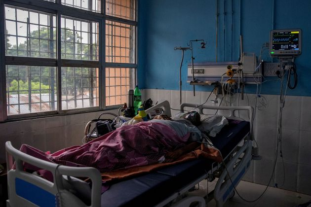 A COVID-19 patient lies on a hospital bed in the Intensive Care Unit of Jawahar Lal Nehru Medical College...