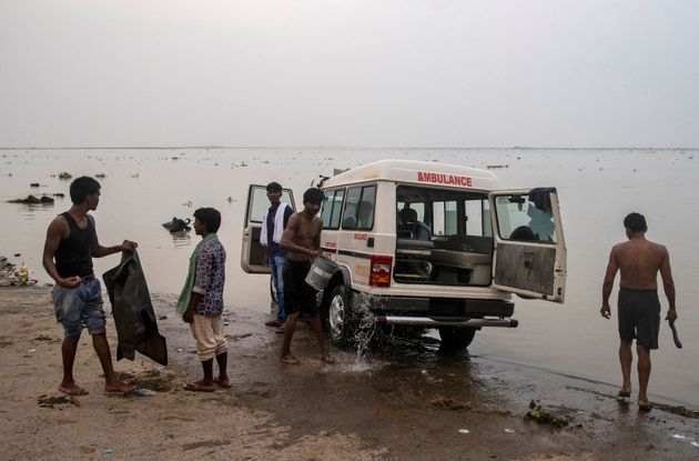 People wash an ambulance on the banks of River Ganga behind Jawahar Lal Nehru Medical College and Hospital,...