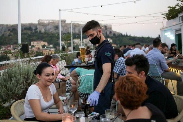 Un camarero les sirve las bebidas a los clientes en una terraza de Atenas (Grecia) el 1 de
