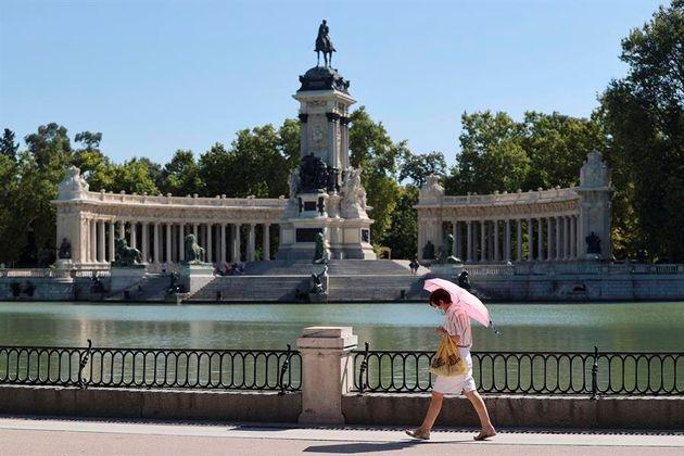 Una mujer pasea por el parque del Retiro, en